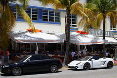 South Beach scene. Miami Beach - June 19: Photo of luxury cars valet parked by roadside restaurants on Ocean Drive Miami Beach Florida June 19, 2015 Stock Images