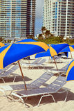 South Beach Umbrellas and Lounge Chairs. Rows of lounge chairs and umbrellas in South Beach, Miami with condos in the background stock photos