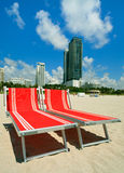 South Beach Umbrellas and Lounge Chairs. Red lounge chairs in South Beach, Miami with condos and art deco hotels in the background stock images