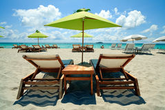 South Beach Umbrellas and Lounge Chairs. Lounge chairs and umbrellas in South Beach, Miami with the ocean and luxury yacht in the background stock photo