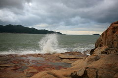 The South China sea off the Vietnamese coast near the city of Nha Trang. A cloudy day with rain clouds and the waves on the rocky coast in January day Stock Photo