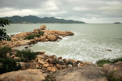 The South China sea off the Vietnamese coast near the city of Nha Trang. A cloudy day with rain clouds and the waves on the rocky coast in January day Royalty Free Stock Image