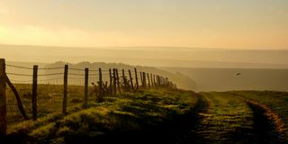 South downs, East Sussex, UK, a country lane track leading into. A silhoutted wooden fence runs in a line on the left leading into four rows of misty rolling stock photography