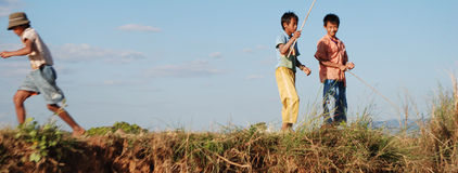 South East Asian kids fishing. Two children fishing in Burma, while another runs. A rural scene near the capital city, Rangoon, typical of the region Stock Image