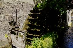 Water mill wheel and moss in water stream stock photos