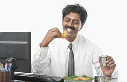 South Indian businessman working in an office and having food Stock Photos