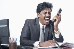 South Indian businessman working in an office and shouting Stock Photography