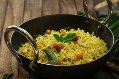 South Indian Curry leaves rice / Karuvepilai sadam served in a Kadai. South Indian Curry leaves rice / Karuvepilai sadam served in Kadai Stock Photo