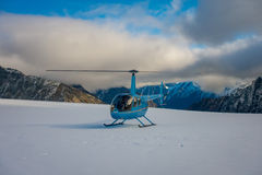 SOUTH ISLAND, NEW ZEALAND- MAY 24, 2017: Close up of blue helicopter waiting over the snow for hunters in South Westland Royalty Free Stock Image