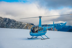 SOUTH ISLAND, NEW ZEALAND- MAY 24, 2017: Close up of blue helicopter waiting over the snow for hunters in South Westland Stock Photography