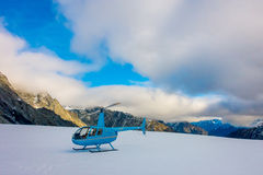 SOUTH ISLAND, NEW ZEALAND- MAY 24, 2017: Close up of blue helicopter waiting over the snow for hunters in South Westland Stock Photos