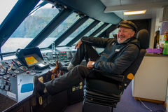 SOUTH ISLAND, NEW ZEALAND- MAY 25, 2017: Close up of a ferry boat pilot command cabin with a smiling captain holding a Royalty Free Stock Photo