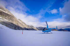 SOUTH ISLAND, NEW ZEALAND- MAY 24, 2017: Helicopter and pilot waiting over the snow for hunters in South Westland`s Royalty Free Stock Photos