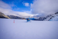 SOUTH ISLAND, NEW ZEALAND- MAY 24, 2017: Helicopter and pilot waiting over the snow for hunters in South Westland`s Stock Image