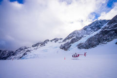 SOUTH ISLAND, NEW ZEALAND- MAY 24, 2017: Helicopter and pilot waiting over the snow for hunters in South Westland`s Royalty Free Stock Photo