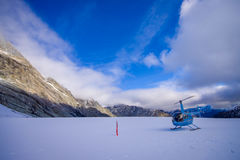 SOUTH ISLAND, NEW ZEALAND- MAY 24, 2017: Helicopter and pilot waiting over the snow for hunters in South Westland`s Stock Photography