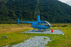 SOUTH ISLAND, NEW ZEALAND - MAY 21, 2017:Helicopter waiting for hunters in South Westland`s Southern Alps, New Zealand Stock Image