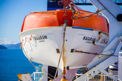 SOUTH ISLAND, NEW ZEALAND- MAY 25, 2017: An orange boat on one side of the ferry just in case of any accident, in New Royalty Free Stock Photo