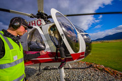 SOUTH ISLAND, NEW ZEALAND- MAY 25, 2017: An unidentified passenger alight from a helicopteter onto the snow above Franz. Josef Glacier, Westland, New Zealand Royalty Free Stock Photos
