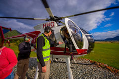 SOUTH ISLAND, NEW ZEALAND- MAY 25, 2017: An unidentified passenger alight from a helicopteter onto the snow above Franz. Josef Glacier, Westland, New Zealand Stock Images