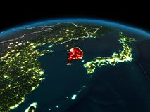 South Korea on Earth at night. Space orbit view of South Korea highlighted in red on planet Earth at night with visible country borders and city lights. 3D Royalty Free Stock Photo