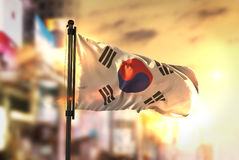 South Korea Flag Against City Blurred Background At Sunrise Back. Light Sky stock photography