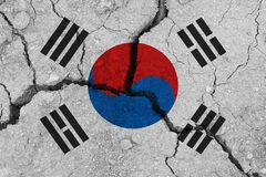 South korea flag on the cracked earth. National flag of South korea. Earthquake or drought concept stock images