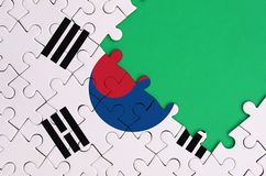 South Korea flag is depicted on a completed jigsaw puzzle with free green copy space on the right side.  stock photography