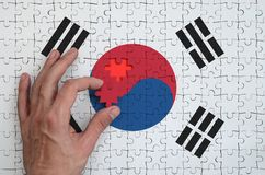 South Korea flag is depicted on a puzzle, which the man`s hand completes to fold.  royalty free stock photo