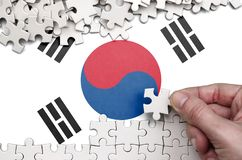 South Korea flag is depicted on a table on which the human hand folds a puzzle of white color.  royalty free stock images