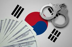 South Korea flag with handcuffs and a bundle of dollars. The concept of illegal banking operations in US currency.  royalty free stock photography