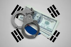 South Korea flag with handcuffs and a bundle of dollars. Currency corruption in the country. Financial crimes.  stock photo