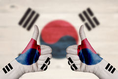 South korea flag painted on female hands thumbs up. With blurry wooden background royalty free stock images