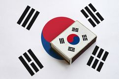 South Korea flag is pictured on a matchbox that lies on a large flag.  stock photography