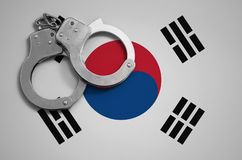 South Korea flag and police handcuffs. The concept of crime and offenses in the country.  royalty free stock photo