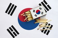 South Korea flag is shown on an open matchbox, from which several matches fall and lies on a large flag.  royalty free stock image