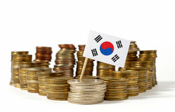 South Korea flag with stack of money coins. South Korea flag waving with stack of money coins royalty free stock images