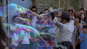 SOUTH KOREA - MAY 29, 2018: Animator Entertain People Crowd with Soap Bubble Performance in Public Street of Seoul stock footage