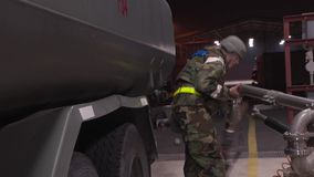 SOUTH KOREA, NOVEMBER 2015, Medium Shot Soldier Gasoline Station Beside Oskosh R-11 Mobile Tanker Truck Unlock Fuel Pipe. Medium shot of a soldier witch stand stock video footage