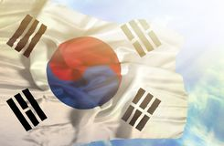 South Korea waving flag against blue sky with sunrays stock images