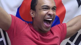 South Korean Fan celebrates holding the flag of South Korea in Slow Motion. High quality royalty free stock photography