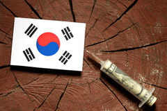 South Korean flag on a stump with syringe injecting money Royalty Free Stock Photo