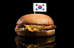 South Korean flag on top of hamburger isolated on black Royalty Free Stock Images