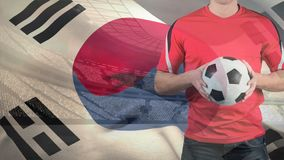 South Korean Flag Video. South Korean Flag against football stadium and football player holding football stock video footage