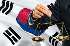 South Korean Judge is holding golden scales of justice with South Korea waving flag background. Equality theme and legal concept stock images
