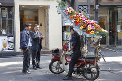 South Korean men talk to man on motorcycle delivering flowers, Seoul South Korea- NOVEMBER 2013 Royalty Free Stock Image