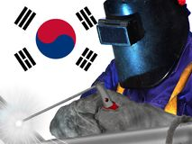 SOUTH KOREAN WELDER WITH BACKGROUND OF HIS FLAG WAVES. WORKER THAT GENERATES WELL-BEING AND RICHES TO HIS COUNTRY AND TO THE WHOLE WORLD stock photography