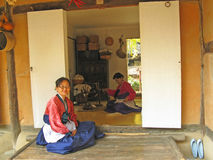 South Korean woman in front of house. A woman in South Korea sits in front of house with another woman working inside Stock Images
