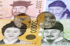 South Korean Won coins on the background of banknotes. South Korean Won coins on the background of South Korean banknotes stock photography