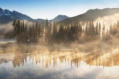 South Sister and Broken Top reflect over the calm waters of Sparks Lake at sunrise in the Cascades Range in Central Oregon, USA in royalty free stock photo